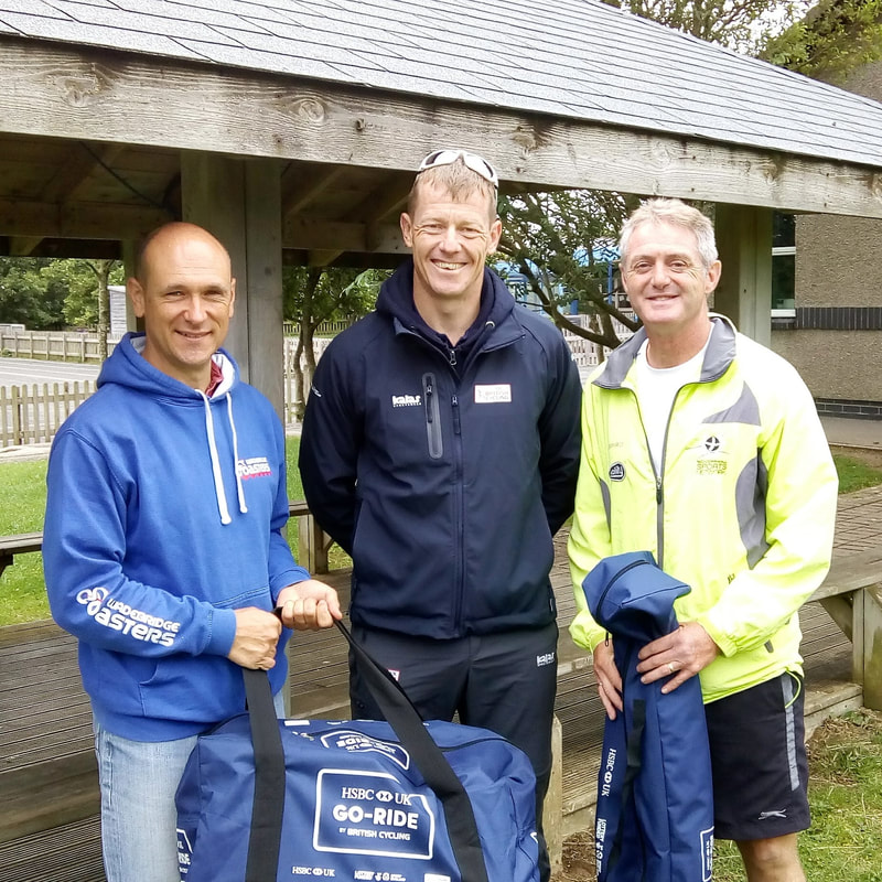 Will Newton from British Cycling presenting an official Go Ride kit bag to coaches Phil and Andy